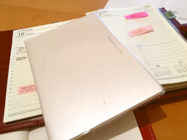 2018年の逆算手帳き表紙です。後ろにみえるのは、あな吉手帳を自分流にアレンジした、1日1頁の手帳です。これは持ち歩けないのが難点。いつも机の上に乗りっばなしです。